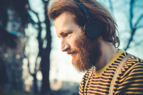 young bearded stylish handsome hipster man listening music with headphones outdoors