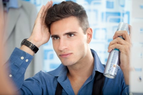 Young man applying hair spray to his hair.